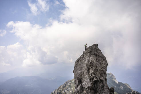 Male hiker standing on top of mountain against cloudy sky, European Alps, Lecco, Italy - MCVF00612