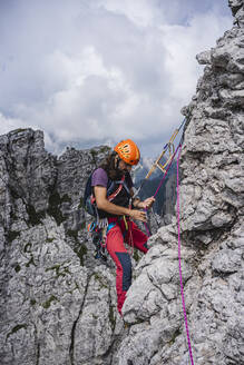 Male mountaineer with rope balancing on mountain, European Alps, Lecco, Italy - MCVF00615