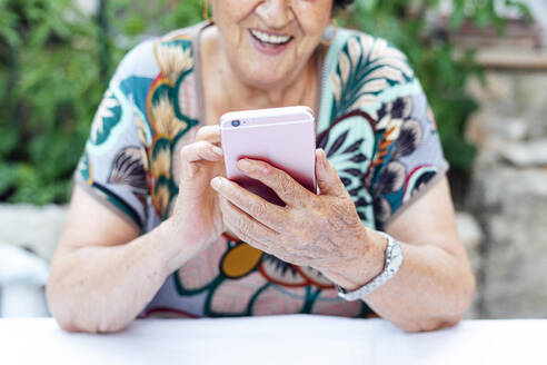 Close-up of senior woman using mobile phone at table while sitting in yard - PGF00004
