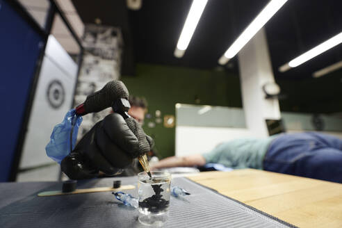Close-up of male artist dipping tattoo machine in water on table - SASF00099