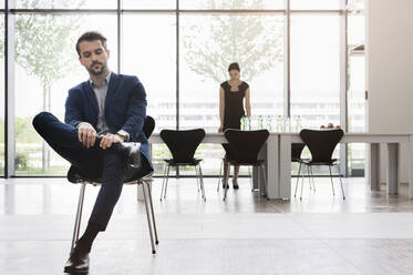 Serious businessman sitting on chair while female coworker working at desk in background - BMOF00459