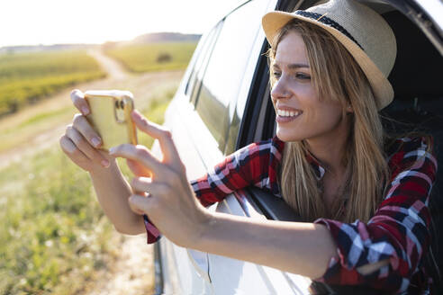 Smiling young woman taking photo through mobile phone while sitting in car - JSRF01132