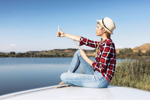 Thoughtful young woman using digital tablet while sitting on car roof - JSRF01138