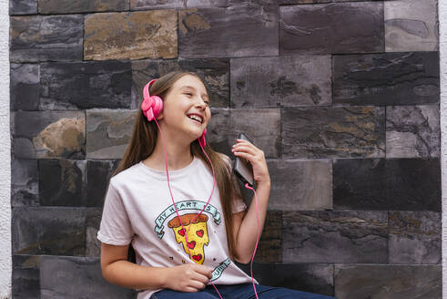 Cheerful girl with headphone listening music while sitting against wall at home - DSIF00128