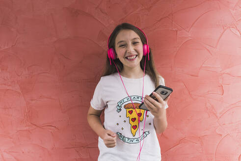 Smiling girl with headphone using mobile phone while standing against wall - DSIF00131