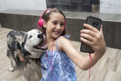 Smiling girl taking selfie with dog while sitting on floor at home - DSIF00134