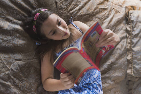 Smiling girl reading book while lying on bed at home - DSIF00137