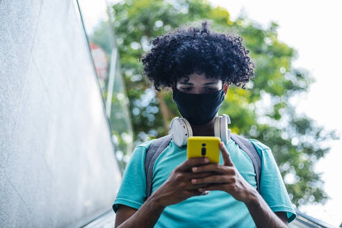 Young man with wearing protective face mask text messaging on smart phone while standing on escalator - XLGF00532