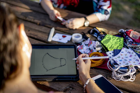 Friends designing face mask on digital tablet while sitting outdoors - OCMF01710