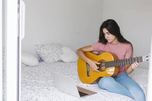 Young woman learning guitar online while sitting at home in bedroom - XLGF00542