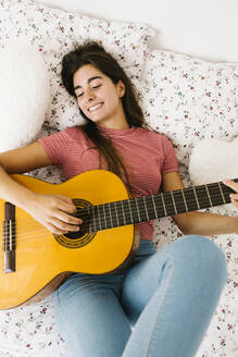 Young woman lying on back while playing guitar in bedroom - XLGF00545