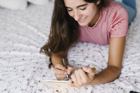 Young woman taking notes in book while lying down on bed at home - XLGF00551