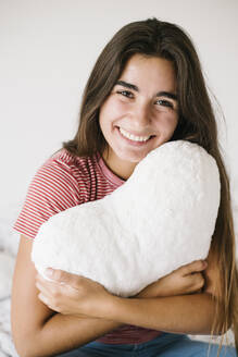 Smiling young woman with heart shape pillow sitting in room at home - XLGF00557