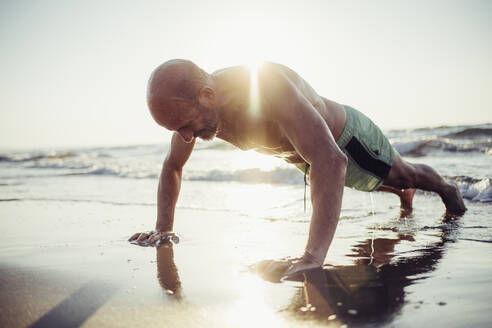 Senior man exercising at beach during sunset - MEUF02071