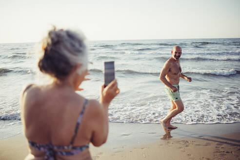 Woman taking photo of man running at beach - MEUF02074