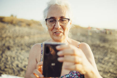 Smiling senior woman using mobile phone while standing at beach - MEUF02077