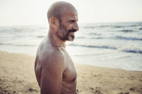 Man smiling while standing at beach - MEUF02080