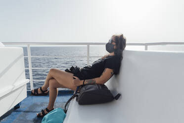 Woman wearing face mask resting while sitting in passenger craft - MEUF02095