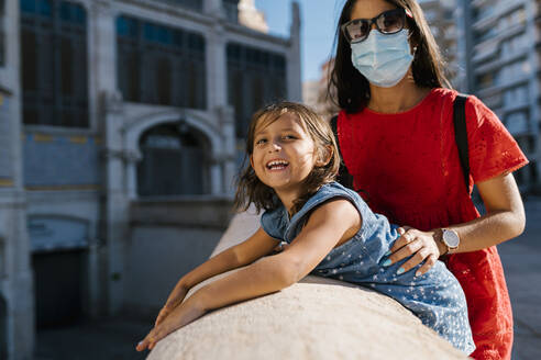 Mother wearing mask standing with daughter by retaining wall in city - EGAF00738