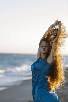 Young woman with hand raised dancing at beach during sunset - GMLF00617