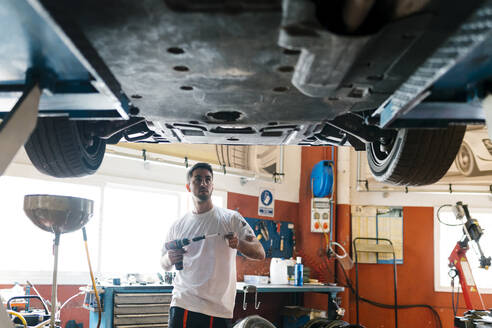Young mechanic holding work tool looking at car while standing in auto repair shop - EGAF00780