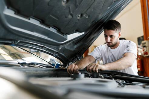 Young man repairing car while standing in auto repair shop - EGAF00786