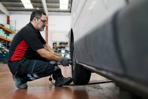 Auto mechanic adjusting car tire in workshop - EGAF00789