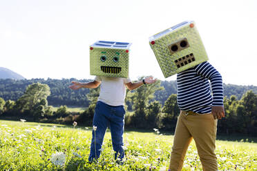 Boys covered face with smiling and robot box while playing in meadow - VABF03515