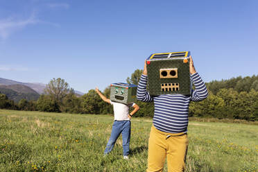 Brothers enjoying playing with robot and smiling cardboard box in meadow - VABF03524