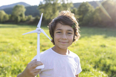 Boy smiling while holding wind turbine toy in meadow - VABF03533