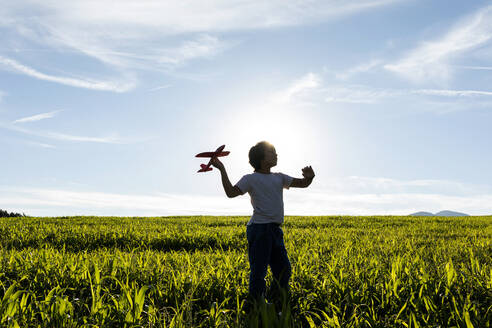 Silhouette of boy playing with airplane toy against clear sky - VABF03536