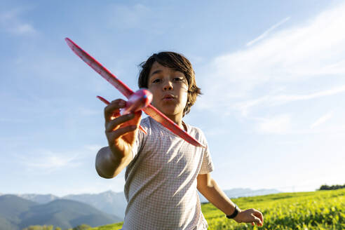 Boy playing with airplane toy while standing against clear sky - VABF03539