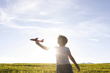 Boy playing with airplane toy while while standing against clear sky - VABF03542