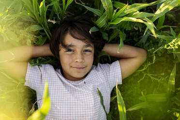 Smiling boy with hands behind head resting on grass in meadow - VABF03548