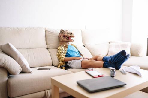 Boy wearing dinosaur mask relaxing on sofa at home - JCMF01447