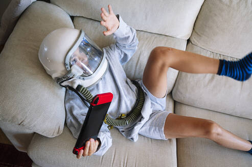 Boy wearing space helmet gesturing while playing video game sofa at home - JCMF01459