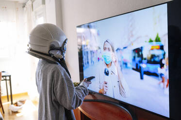 Boy wearing space helmet watching journalist mother on TV while standing at home - JCMF01462