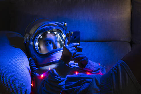 Boy wearing space helmet using mobile phone while relaxing on sofa in illuminated home - JCMF01465