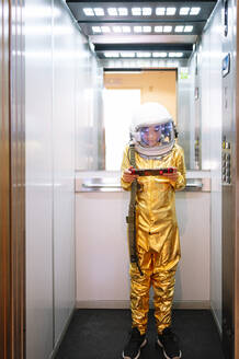 Boy wearing space suit playing video game while standing in open elevator - JCMF01471