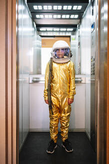 Boy wearing space suit standing in open elevator - JCMF01474