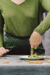 Close-up of woman with finger in guacamole on table at home - ERRF04435