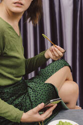 Close-up of woman holding smart phone eating guacamole and pretzel while sitting on table at home - ERRF04438