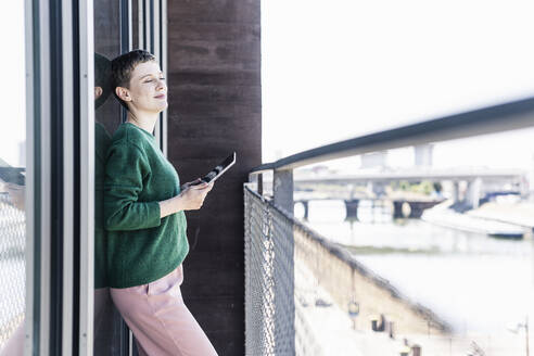 Businesswoman with eyes closed holding digital tablet while standing in balcony - UUF21541
