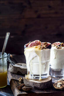Two glasses of Greek yogurt with honey, figs and walnuts - SBDF04368