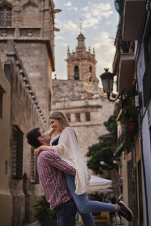 Happy man picking up woman while standing in city - SASF00122