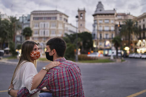 Couple wearing protective mask sitting on street in city - SASF00125