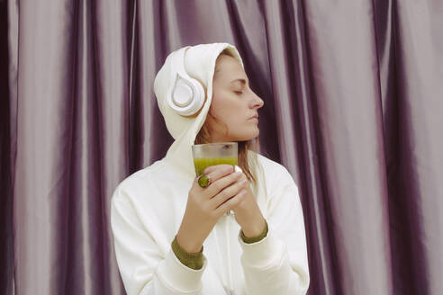 Woman with green juice listening music over headphones while standing against curtain at home - ERRF04448