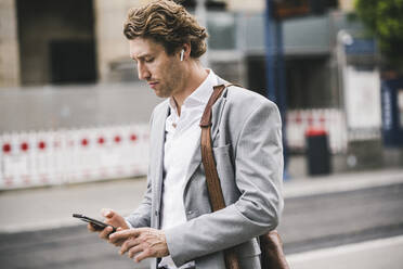 Businessman using mobile phone while standing in city - UUF21567