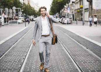 Smiling man talking on mobile phone while walking at tramway in city - UUF21570