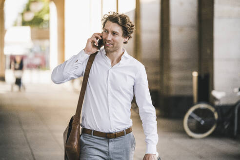 Man smiling while talking on mobile phone in city - UUF21582